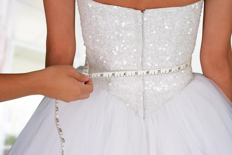 Woman in a wedding dress getting measured - Should You Diet Before Your Wedding?